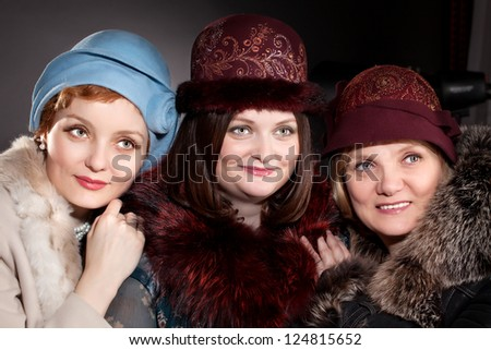 elegant three women  mother and adult daughters wearing dark  hat in retro style and fur - stock photo