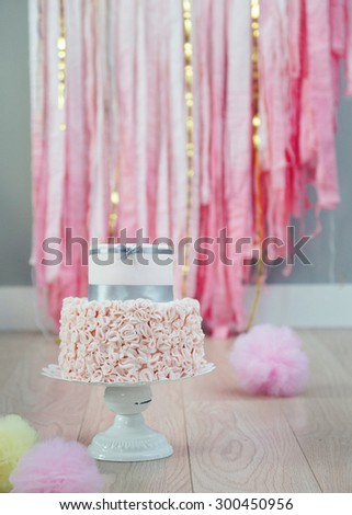 Elegant two-tier birthday or wedding cake with ruffled fondant bottom, decorated with grey satin ribbon. Pastel pompoms on the wooden floor, fabric streamers in the background.  - stock photo