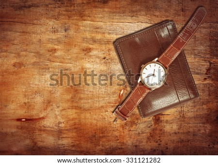 elegant watch and wallet on table - stock photo