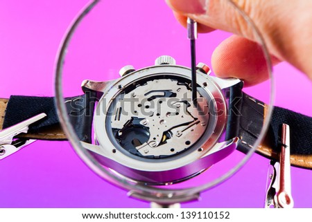 Elegant watch repaired using a magnifier with three handles - stock photo