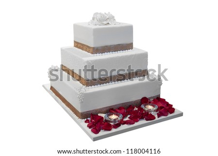 Elegant wedding cake decorated with rose petals and candles, isolated on white - stock photo