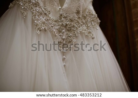 Elegant Wedding Dress Hanging with Textured Background