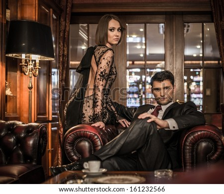 Elegant well-dressed couple in luxury interior - stock photo