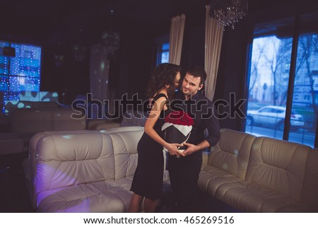 Elegant well-dressed man presenting flowers to a woman in luxury interior