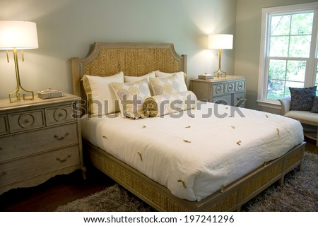Elegant well lighted bedroom with dresser chest, lamps and headboard. - stock photo