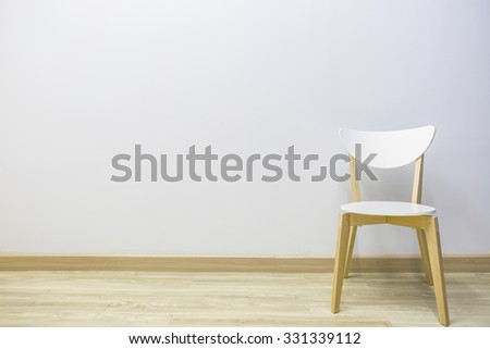 Elegant white chair in an empty room with wooden floor.