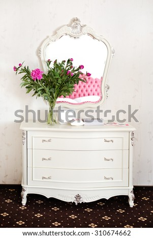 Elegant white commode with beautiful mirror and peony flowers  - stock photo