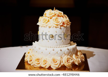Elegant white wedding cake with roses in 2 tiers