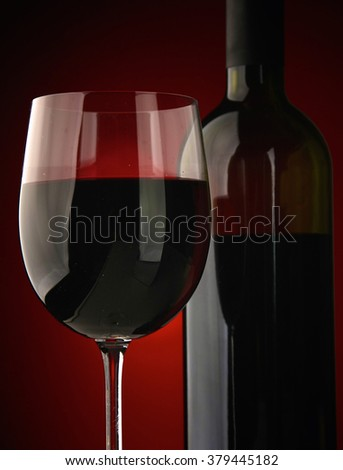 Elegant wine glass and a wine bottle in black background