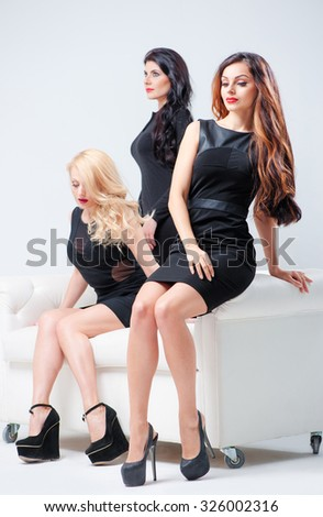 Elegant woman. Group portrait of three attractive caucasian models wearing black dresses sitting on the white sofa