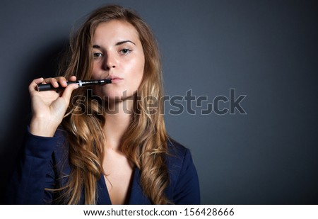 Elegant woman holding and smoking e-cigarette - stock photo