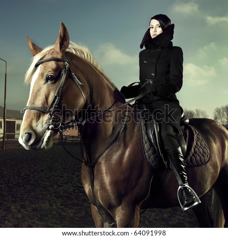 Elegant woman in a black coat riding on a brown horse - stock photo
