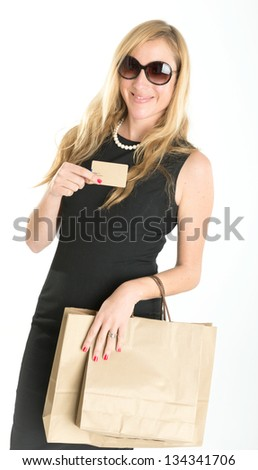 Elegant woman in a black dress holding shopping bags and a credit card - stock photo