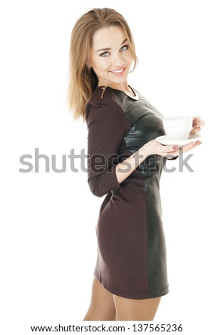 Elegant  woman in a  leather short dress   holding cup and saucer against white background.