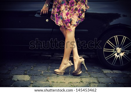 elegant woman in high heel shoes getting into car - stock photo