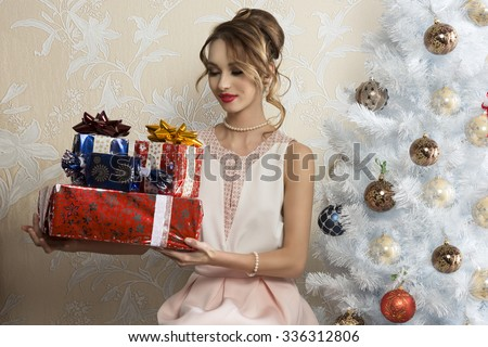 elegant woman in interior Xmas portrait sitting near decorated tree with some Christmas presents in the hands and looking them with satisfy expression  - stock photo