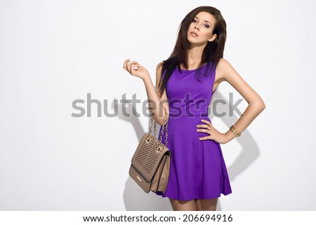 elegant woman in purple dress holding handbag posing in the studio - stock photo