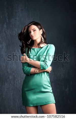 elegant woman in short green dress on dark background studio shot - stock photo