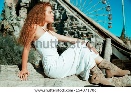 elegant woman in white dress sitting on the stones . horizontal outdoors shot. - stock photo