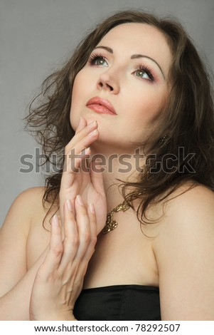 Elegant woman looking up and holding hands near face - stock photo