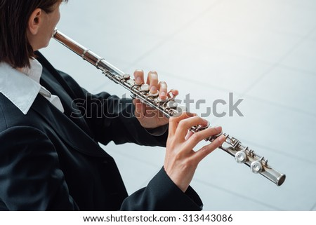 Elegant woman playing a transverse flute, classical music professional