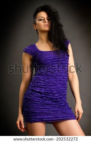 Elegant woman Portrait of pretty brunette girl who wears a blue dress on a gray background. Blue dress on a gray background. - stock photo