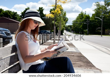 Elegant woman reading a newspaper outside. - stock photo