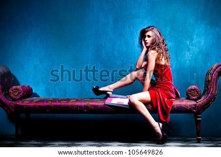 elegant woman sit on recamier reading magazine, studio shot, full body shot - stock photo