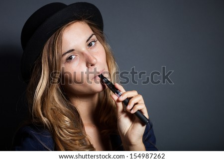 Elegant woman smoking e-cigarette, wearing suit and hat - stock photo