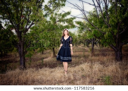 elegant woman stand in front of orchard, full body shot, autmn day - stock photo