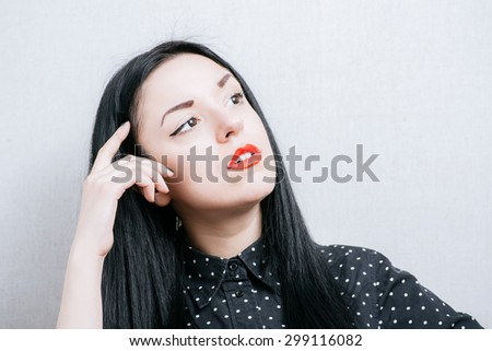 Elegant woman thinks finger to her temple. On a gray background. - stock photo