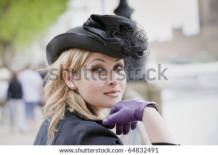 Elegant woman wearing  hat and gloves