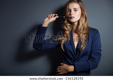 Elegant woman with e-cigarette, wearing suit - stock photo