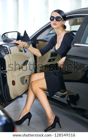 Elegant woman with long legs in car - stock photo