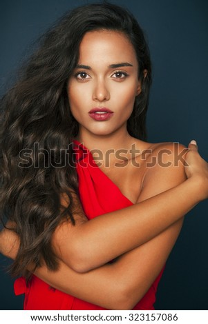 Elegant woman with long wavy hair and red lips wearing red dress .studio shot, Vertical - stock photo