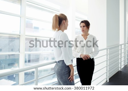 Elegant women entrepreneurs speaking about something personal while standing near office window, two European female managers dressed in formal wear have met in company corridor during work break   - stock photo