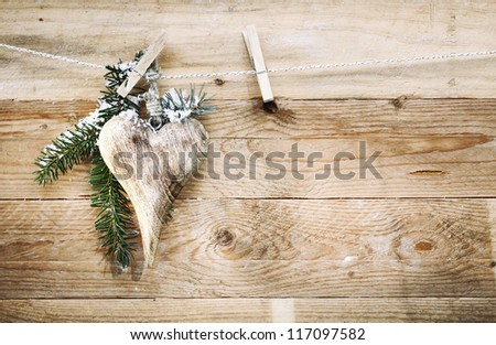 Elegant wooden Valentines, anniversary or Christmas heart hanging from a clothespeg with snow covered pine foliage against wooden boards with texture, woodgrain and copyspace - stock photo