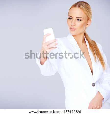 Elegant young blond woman in a sexy white suit standing texting on her mobile against a grey studio background with copyspace