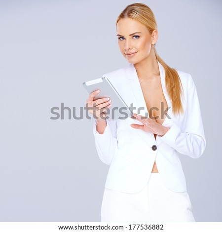 Elegant young blond woman in a sexy white suit standing texting on her mobile against a grey studio background with copyspace - stock photo