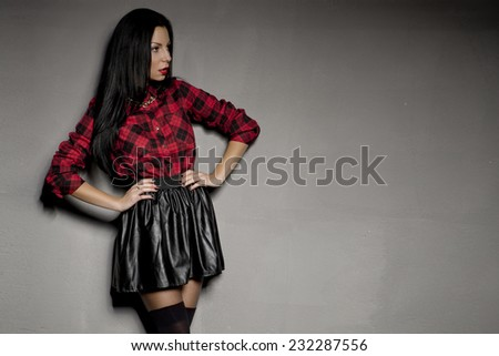 Elegant young brunette woman posing in beautiful black skirt and red shirt. Girl with long hair.