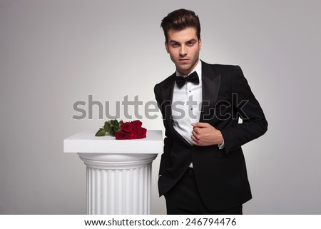 Elegant young business man fixing his tuxedo near a white column with a roses on top of it. - stock photo
