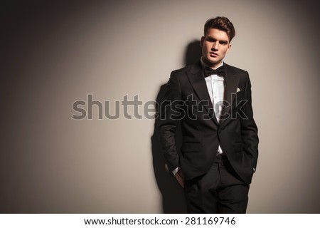 Elegant young business man leaning on a grey wall with his hands in pockets. - stock photo