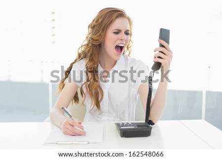 Elegant young businesswoman shouting into the phone at a bright office - stock photo