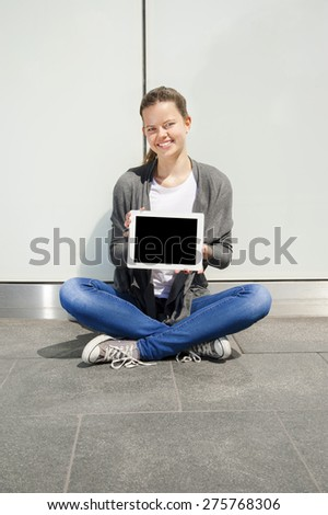 Elegant young businesswoman using tablet leaning to wall - stock photo