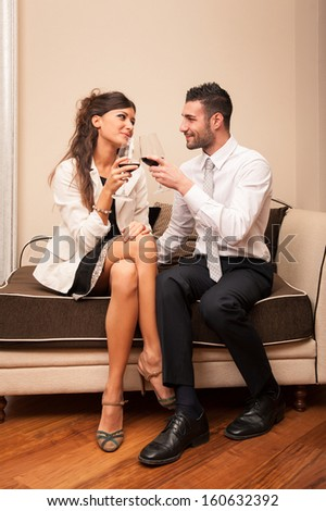 Elegant young couple drinking a glass of wine sit on a sofa. - stock photo