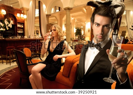elegant young couple drinking wine in a luxury interior - stock photo