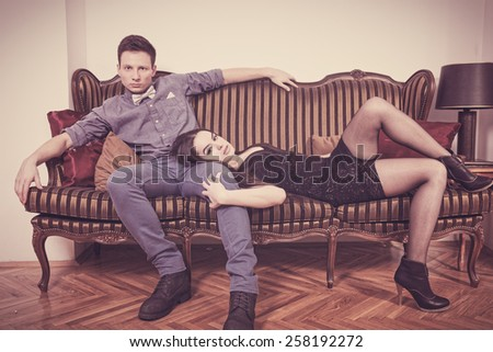 Elegant  young couple in love lying and sitting on a vintage couch or two-seater. Glamour man and woman in luxury room. Vintage retro photo. Fashion style - stock photo