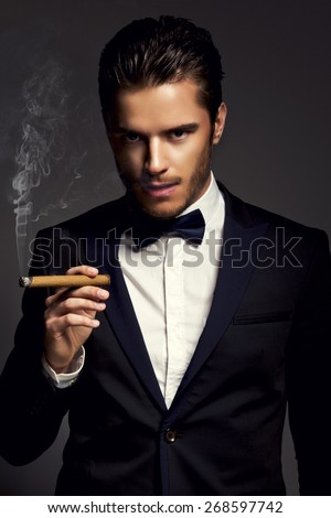 elegant young fashion man in a suit smoking cigar looking at the camera. on dark gray background - stock photo