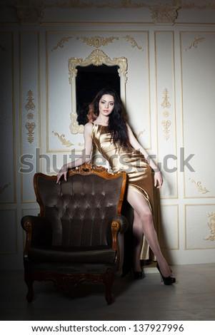 Elegant young girl in classic interior, studio shot - stock photo
