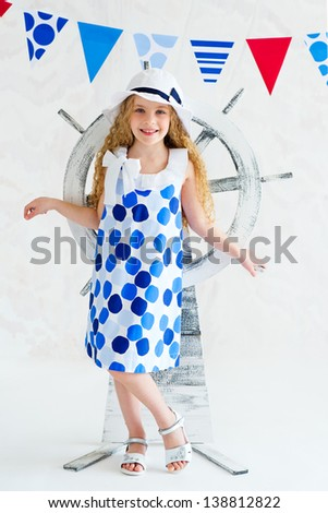 Elegant young girl wearing fashion spotted dress standing in front of decorative wooden steer wheel - stock photo